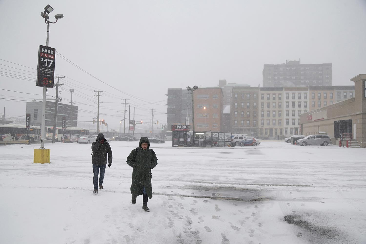 <div class='meta'><div class='origin-logo' data-origin='AP'></div><span class='caption-text' data-credit='AP Photo/Seth Wenig'>People makes their way across an almost empty parking lot in Hoboken, N.J., Thursday, Jan. 4, 2018.</span></div>