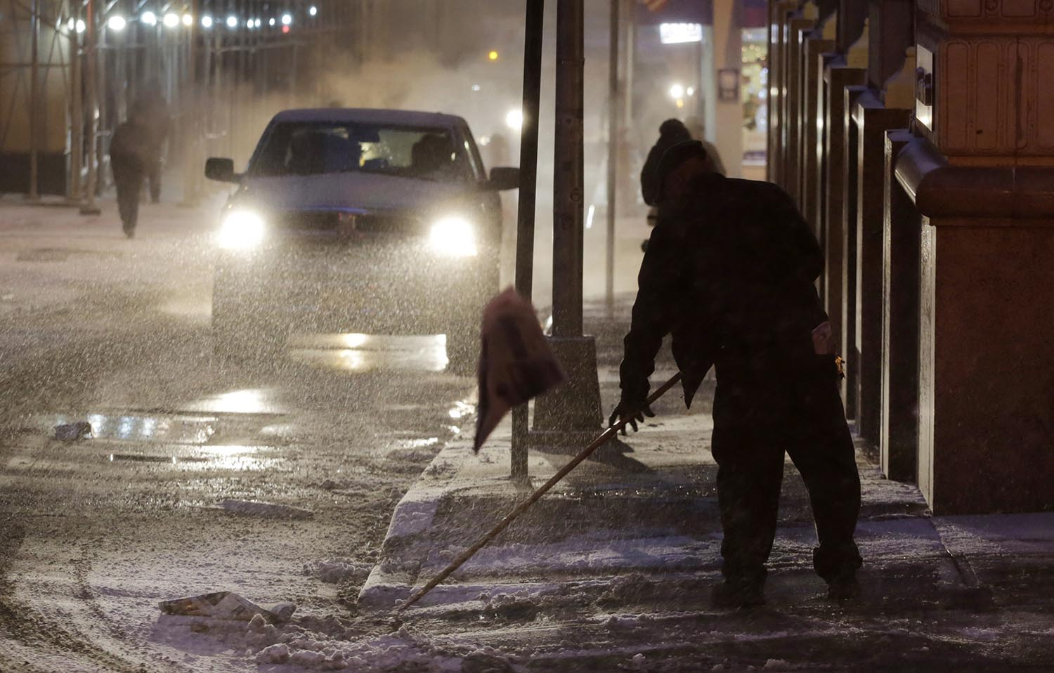 <div class='meta'><div class='origin-logo' data-origin='AP'></div><span class='caption-text' data-credit='AP Photo/Mark Lennihan'>A man clears snow from a sidewalk, Thursday, Jan. 4, 2018, in New York.</span></div>