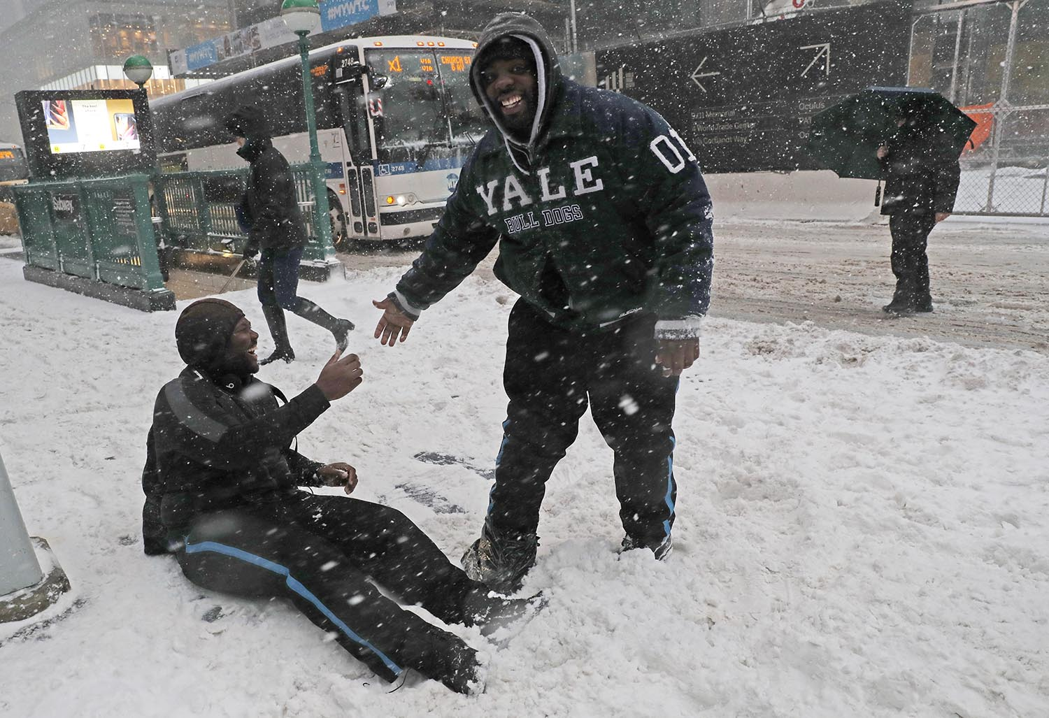 <div class='meta'><div class='origin-logo' data-origin='AP'></div><span class='caption-text' data-credit='AP Photo/Kathy Willens'>Marcus Greenaway, right, laughs as he helps his friend Psyquan Campbell up after Cambell slipped in the snow crossing a street in lower Manhattan in New York, Jan. 4, 2018.</span></div>