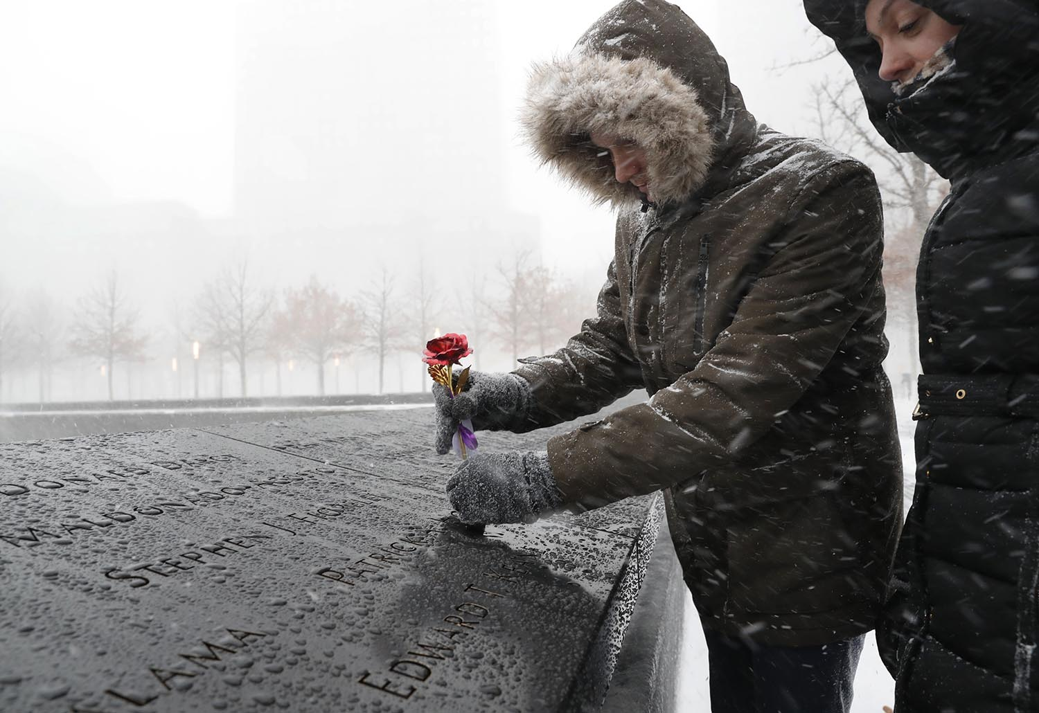 "<div class=""meta image-caption""><div class=""origin-logo origin-image ap""><span>AP</span></div><span class=""caption-text"">Tara Chandler, right, watches her husband Joshua place a metal rose on the border of one of the fountains at the National September 11 Memorial and Museum in New York, Jan 4, 2018. (AP Photo/Kathy Willens)</span></div>"
