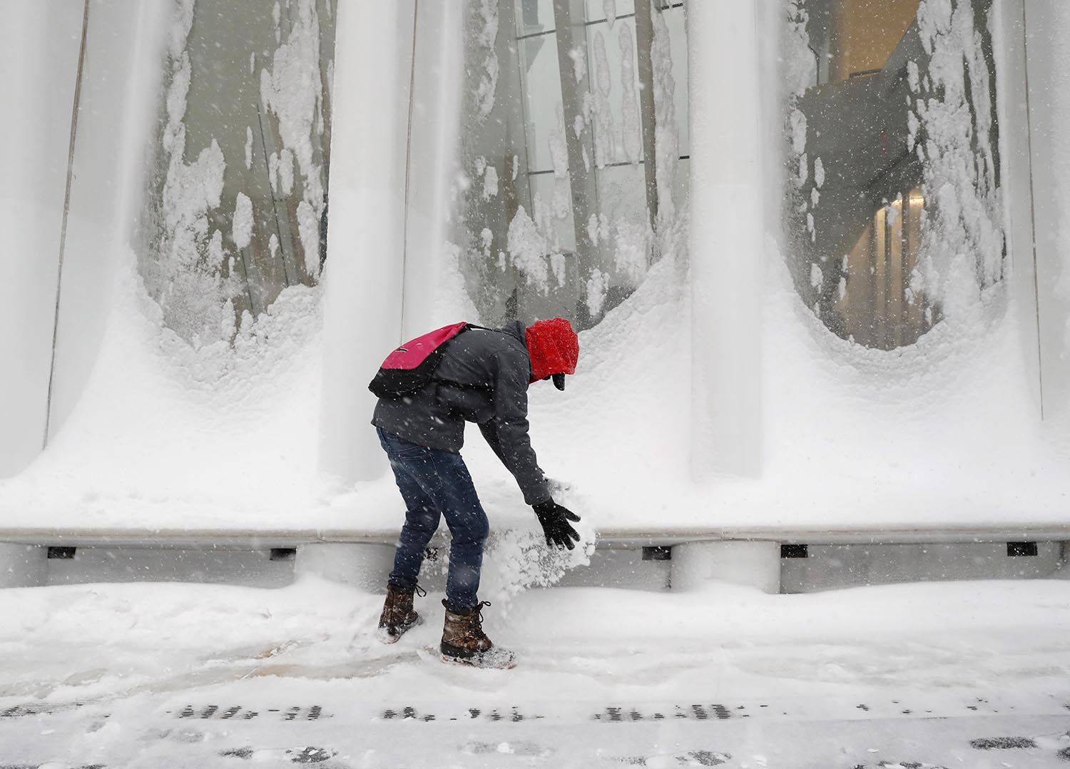 <div class='meta'><div class='origin-logo' data-origin='AP'></div><span class='caption-text' data-credit='AP Photo/Kathy Willens'>A passerby stops to play with drifting snow that accumulated in the windows outside the Oculus at the World Trade Center's transportation hub in Lower Manhattan, Jan. 4, 2018.</span></div>