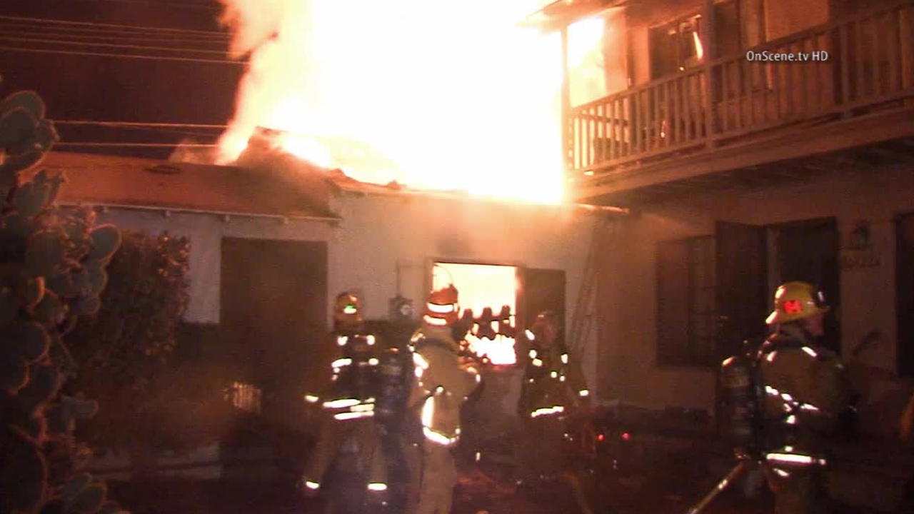 Firefighters work to put out a fire that broke out at a carport in a South Los Angeles apartment complex on Sunday, Aug. 30, 2014.