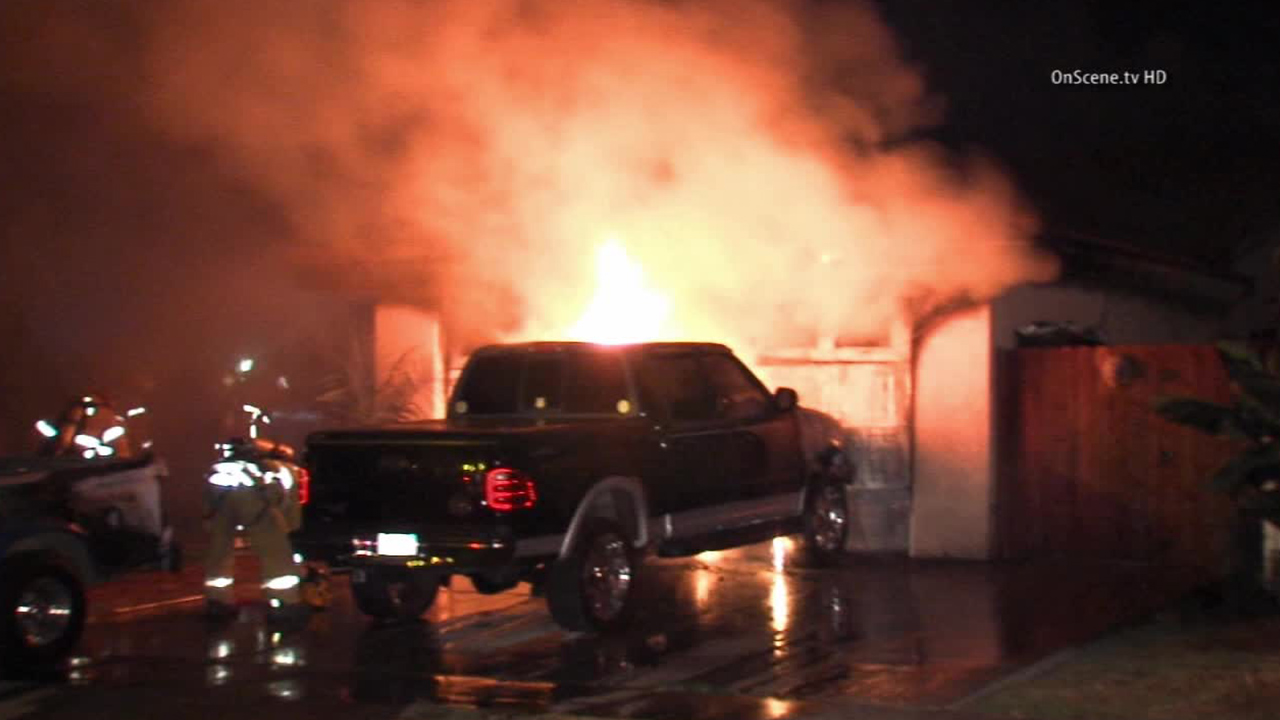 A truck catches fire and the flames spread to a garage in Santa Ana on Sunday, Aug. 31, 2014.