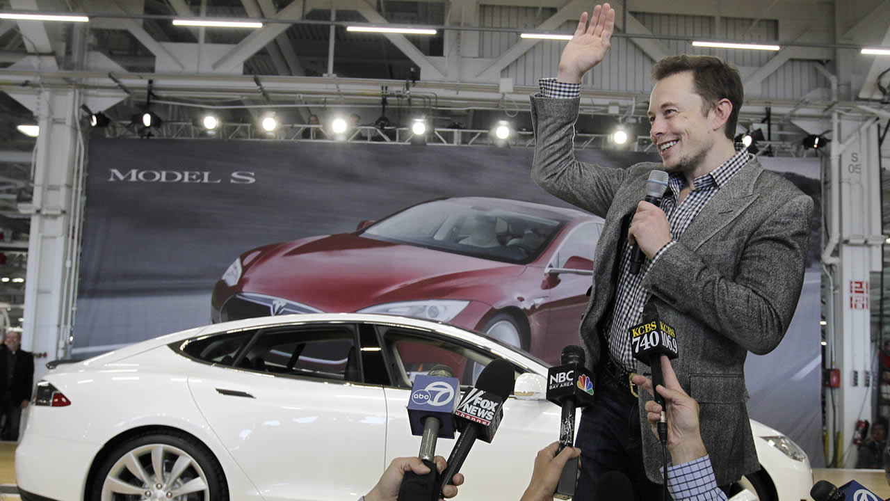 In this June 22, 2012 file photo, Tesla CEO Elon Musk waves during a rally at the Tesla factory in Fremont, Calif. (AP Photo/Paul Sakuma, File)