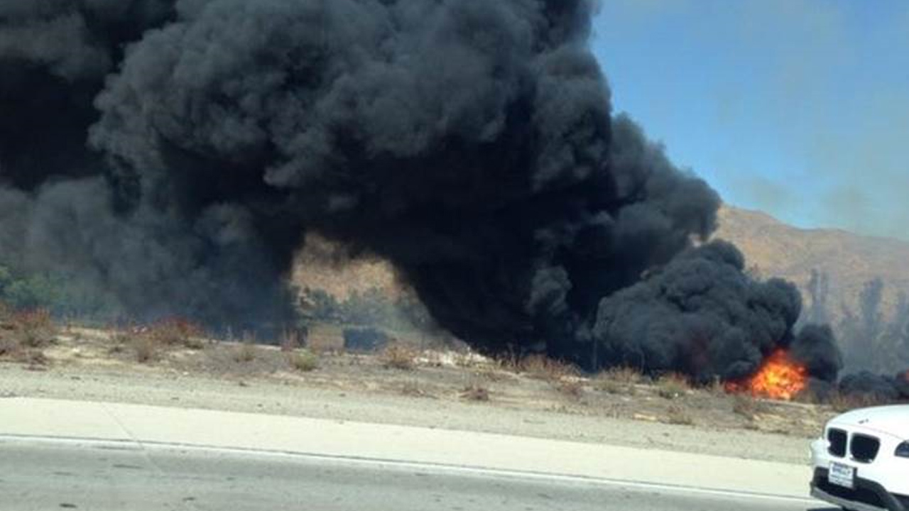 A brush fire burns off the northbound 15 Freeway in Corona on Monday, Sept. 1, 2014.