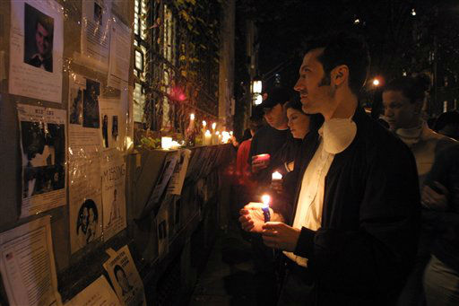 "<div class=""meta image-caption""><div class=""origin-logo origin-image none""><span>none</span></div><span class=""caption-text"">In this September 14, 2001 photograph, a man hold a candles and looks at missing person posters after the September 11 terrorist attacks on the World Trade Center in New York City. (AP Photo/ David Karp)</span></div>"