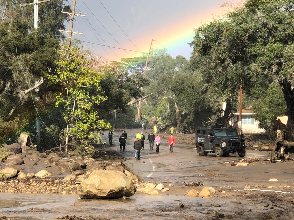 "<div class=""meta image-caption""><div class=""origin-logo origin-image none""><span>none</span></div><span class=""caption-text"">""A rainbow forms above Montecito while law enforcement and the curious survey the destruction on Hot Springs Road in Montecito."" (Santa Barbara County Fire)</span></div>"