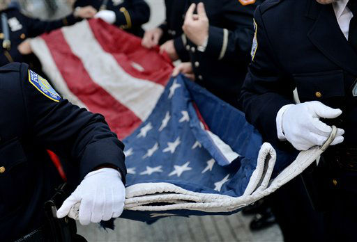 "<div class=""meta image-caption""><div class=""origin-logo origin-image none""><span>none</span></div><span class=""caption-text"">Port Authority police officers carry an American flag that flew over at the World Trade Center towers, in 2012. (AP Photo/ Justin Lane)</span></div>"