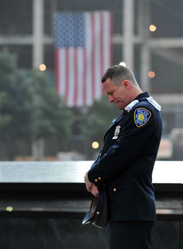 "<div class=""meta image-caption""><div class=""origin-logo origin-image none""><span>none</span></div><span class=""caption-text"">Daniel Henry, a Port Authority police officer, pauses during a moment of silence at 9:01 a.m. at the south reflecting pool in 2013. (AP Photo/ Stan Honda)</span></div>"