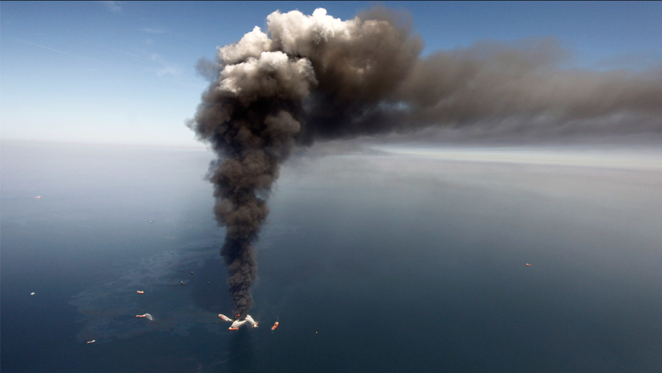 FILE - Wednesday, April 21, 2010: Oil can be seen in the Gulf of Mexico, more than 50 miles southeast of Louisiana's tip, from fires on BP's Deepwater Horizon offshore oil rig.