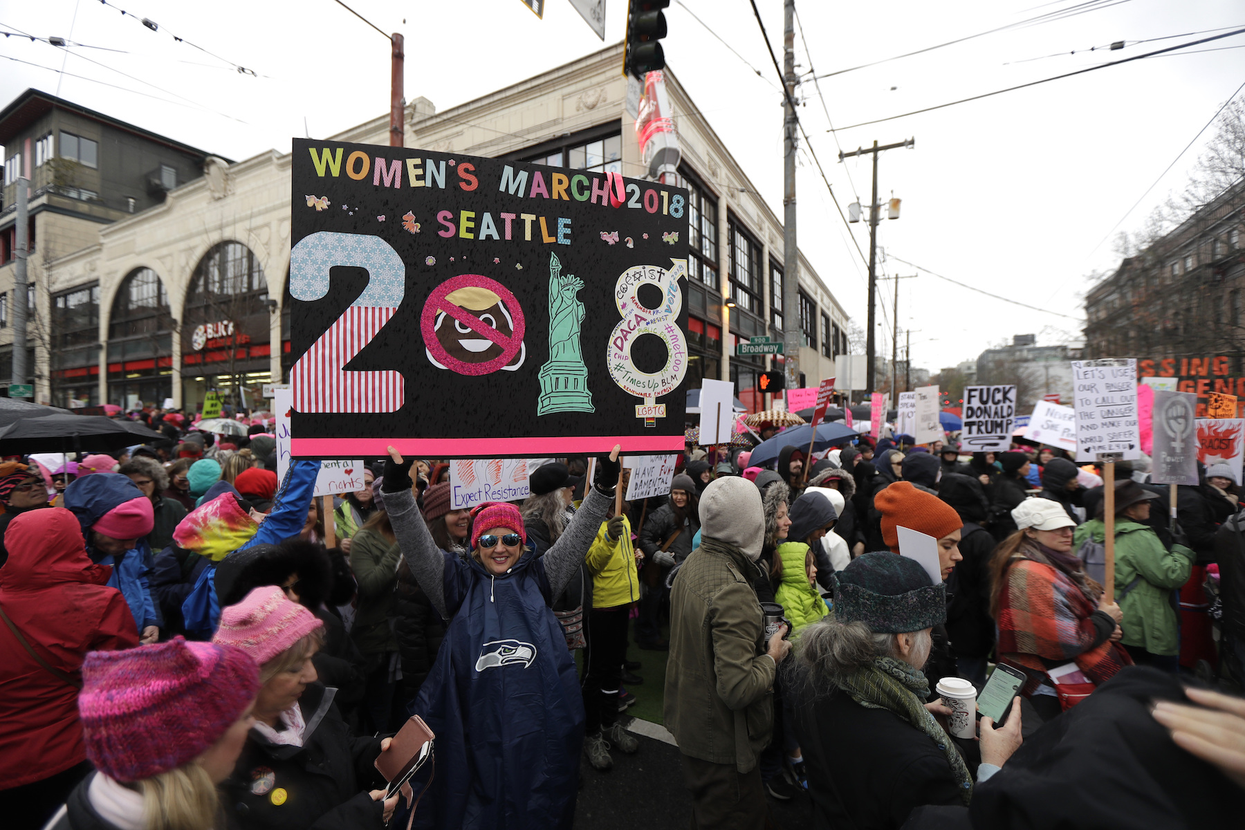 <div class='meta'><div class='origin-logo' data-origin='AP'></div><span class='caption-text' data-credit='AP Photo/Ted S. Warren'>A woman holds as sign as she takes part in a Women's March in Seattle, Saturday, Jan. 20, 2018. The march was one of dozens planned across the U.S. over the weekend.</span></div>