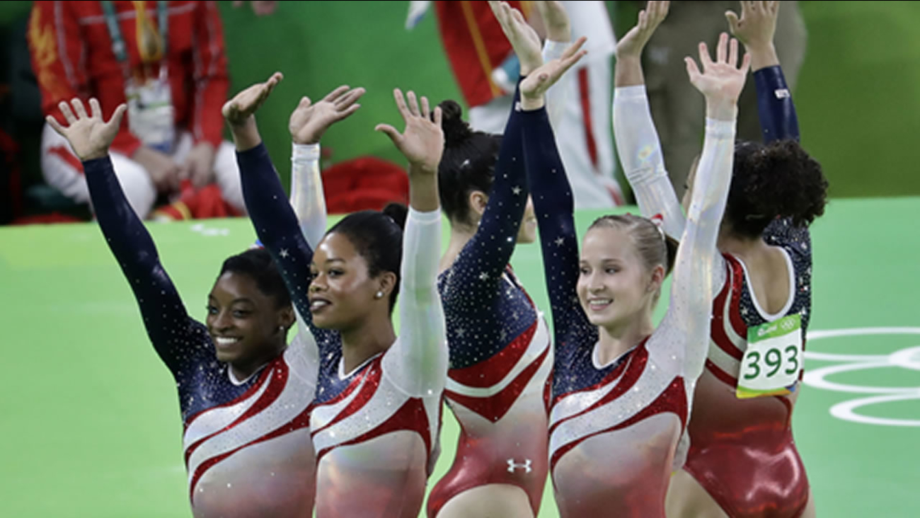 U.S. gymnasts, left to right, Simone Biles, Gabrielle Douglas, Aly Raisman, Madison Kocian, and Lauren Hernandez wave at 2016 Summer Olympics in Rio de Janeiro, Aug. 9, 2016.