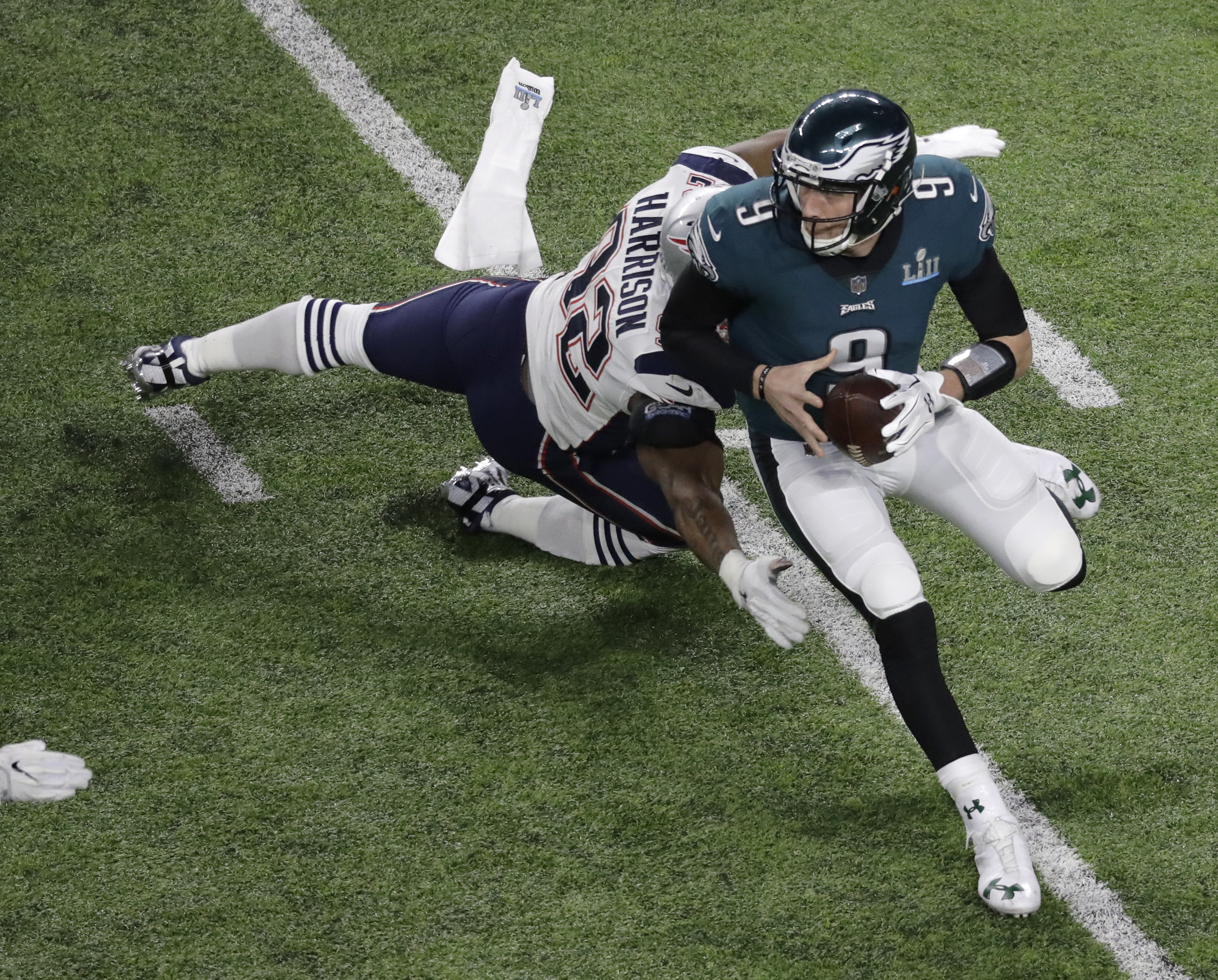"<div class=""meta image-caption""><div class=""origin-logo origin-image ap""><span>AP</span></div><span class=""caption-text"">Philadelphia Eagles quarterback Nick Foles (9) runs around New England Patriots outside linebacker James Harrison during the first half of the NFL Super Bowl 52 football game. (AP Photo/Eric Gay)</span></div>"