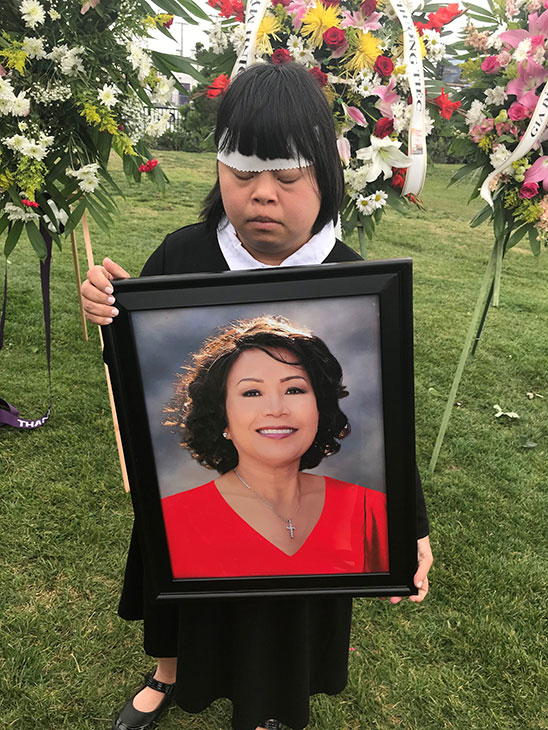 Helen Huynh's daughter, Tiffany Huynh, holds a photo of her mother at the Garden Grove woman's burial in Orange County on Saturday, Feb. 10, 2018.