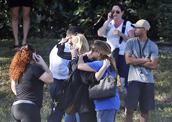 <div class='meta'><div class='origin-logo' data-origin='AP'></div><span class='caption-text' data-credit='AP Photo/Wilfredo Lee'>Anxious family members wait for news of students as two people embrace, Wednesday, Feb. 14, 2018, in Parkland, Fla.</span></div>
