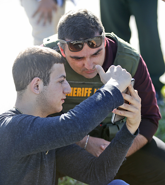 <div class='meta'><div class='origin-logo' data-origin='AP'></div><span class='caption-text' data-credit='AP Photo/Wilfredo Lee'>A student shows a law enforcement officer a photo or video from his phone, Wednesday, Feb. 14, 2018, in Parkland, Fla.</span></div>