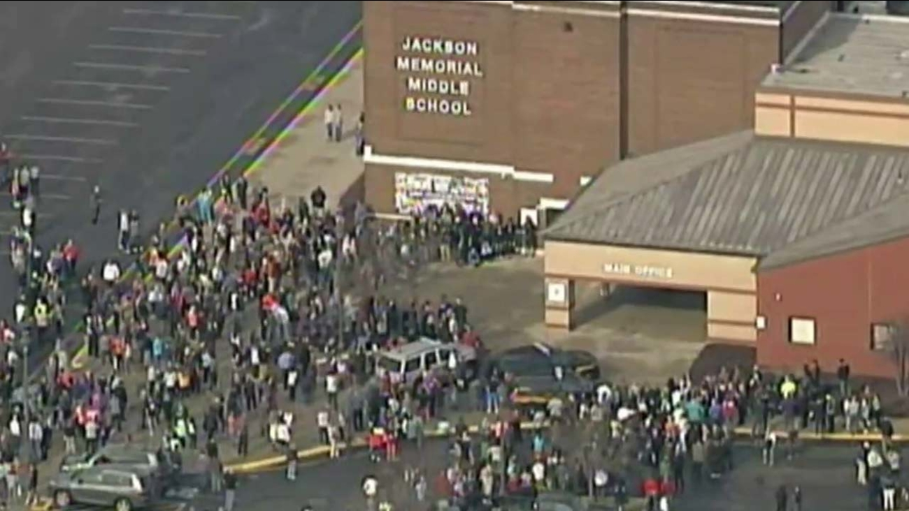 A crowd gathers outside a school in Ohio, where a student apparently shot himself inside a bathroom on Tuesday, Feb. 20, 2018.