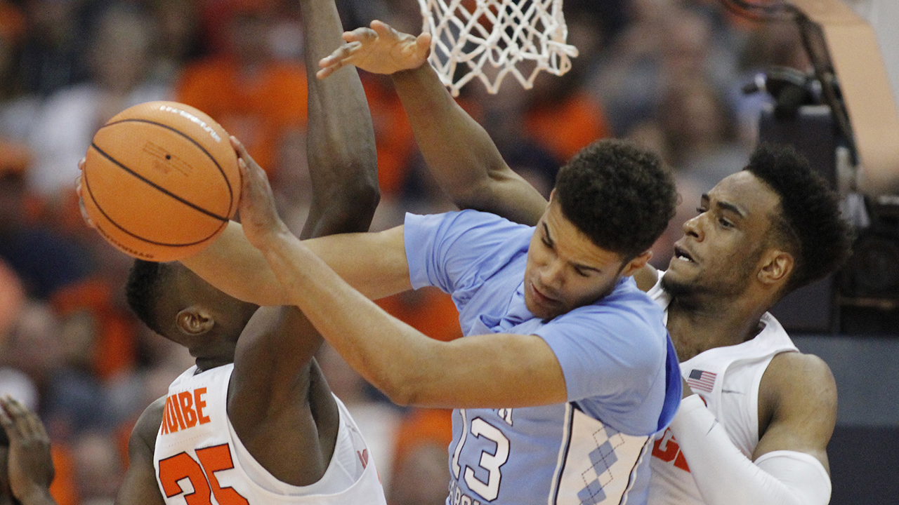 North Carolina's Cameron Johnson, center, grabs a rebound from Syracuse's Bourama Sidibe, left, and Syracuse's Oshae Brissett on Wednesday.