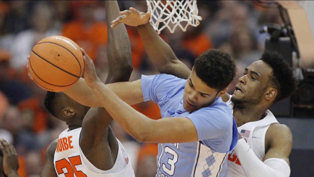 North Carolina's Cameron Johnson, center, grabs a rebound from Syracuse's Bourama Sidibe, left, and Syracuse's Oshae Brissett on Wednesday.