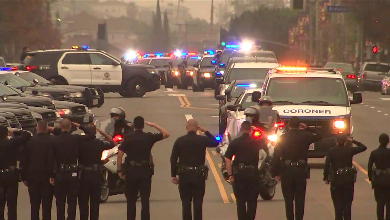 Fellow officers salute a procession escorts a slain Pomona police officer to the Los Angeles County coroner's office on Saturday, March 3, 2018.