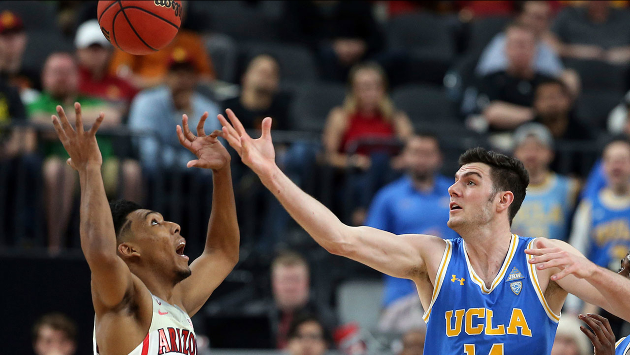 UCLA's Gyorgy Goloman and Arizona's Allonzo Trier reach for a loose ball during the semifinals of the Pac-12 men's tournament Friday, March 9, 2018, in Las Vegas.