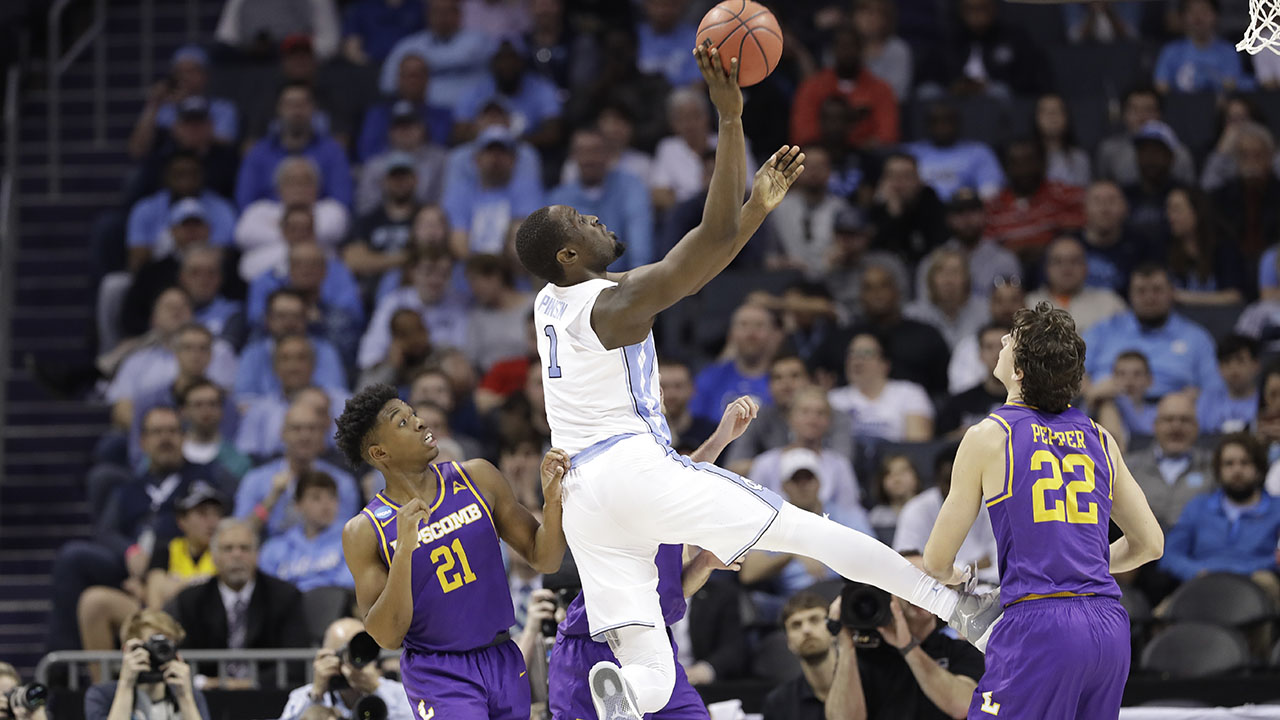 North Carolina's Theo Pinson shoots between Lipscomb's Eli Pepper (22) and Kenny Cooper (21).