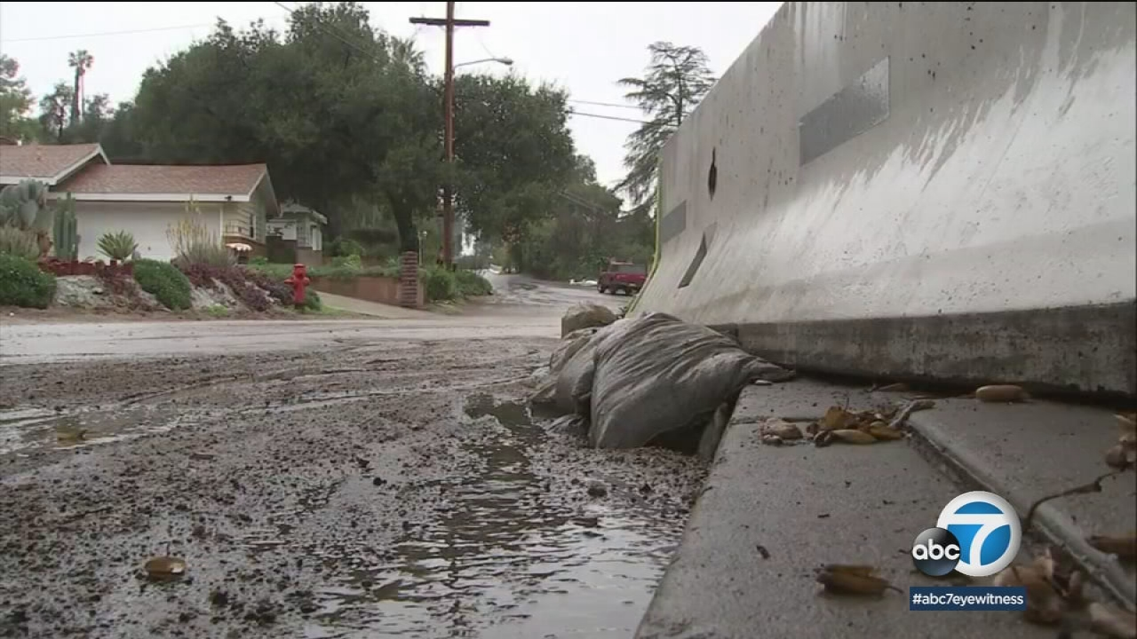 Sandbags and K-rails show murky and debris water flowing down a street in Los Angeles County amid a storm.