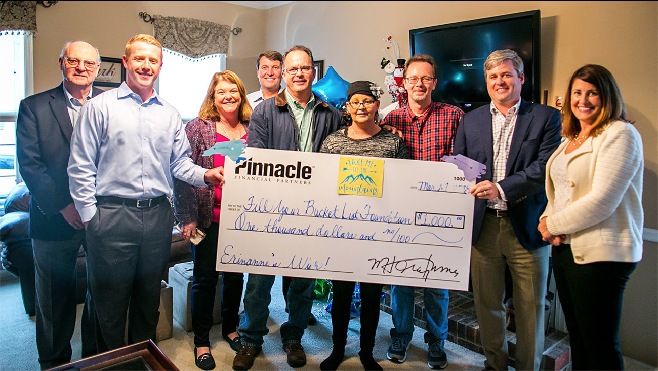 Erinanne Clark, center, and her husband, Charles (in red shirt) are getting to go on their dream trip to Asheville thanks to Pinnacle.