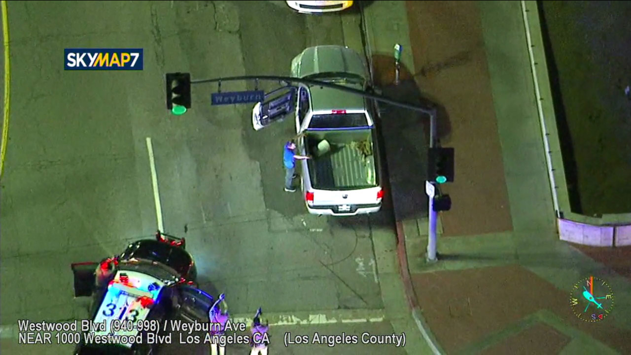A suspect who led authorities on a short chase on the 405 Freeway surrenders in Westwood on Friday, March 23, 2018.
