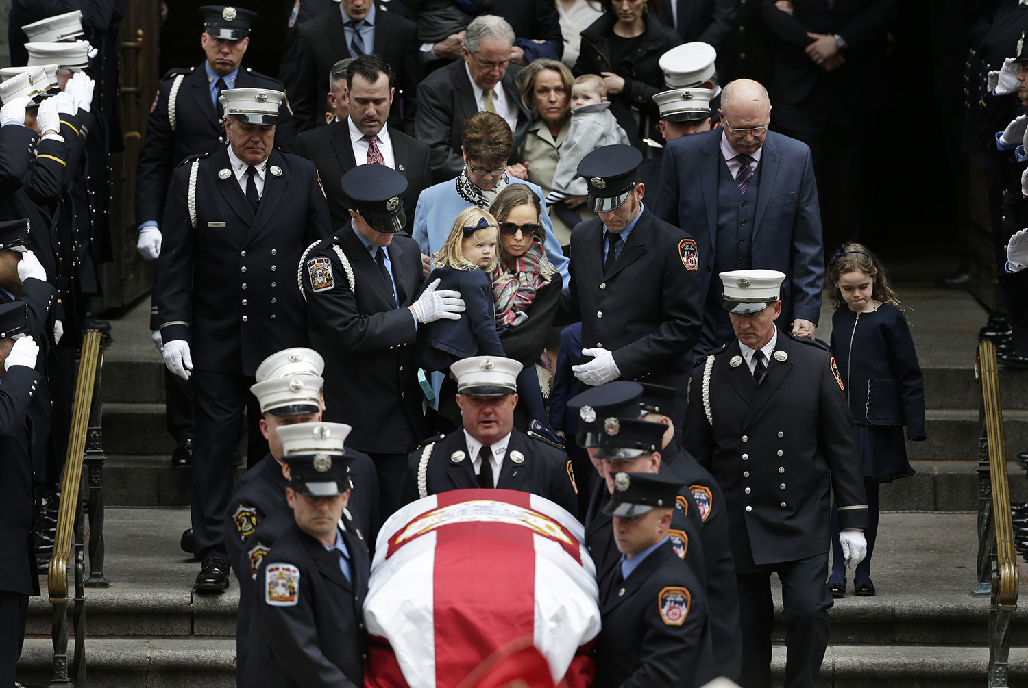 <div class='meta'><div class='origin-logo' data-origin='AP'></div><span class='caption-text' data-credit='Seth Wenig'>The family of firefighter Michael Davidson, including his wife Eileen Davidson, center, follow the casket out of St. Patrick's Cathedral after his funeral.</span></div>