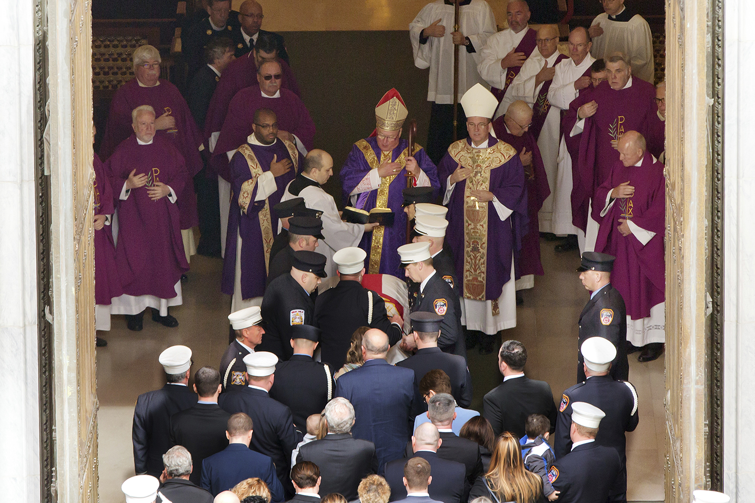 <div class='meta'><div class='origin-logo' data-origin='AP'></div><span class='caption-text' data-credit='Richard Drew'>Archbishop Timothy Dolan, center, presides over the casket of New York City firefighter Michael Davidson as it enters St. Patrick's Cathedral.</span></div>