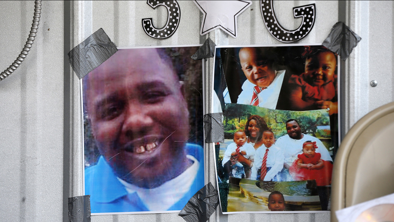 Photos of Alton Sterling are seen July 6, 2016, on a makeshift memorial outside the Triple S convenience store in Baton Rouge, La., where he was fatally shot by police.