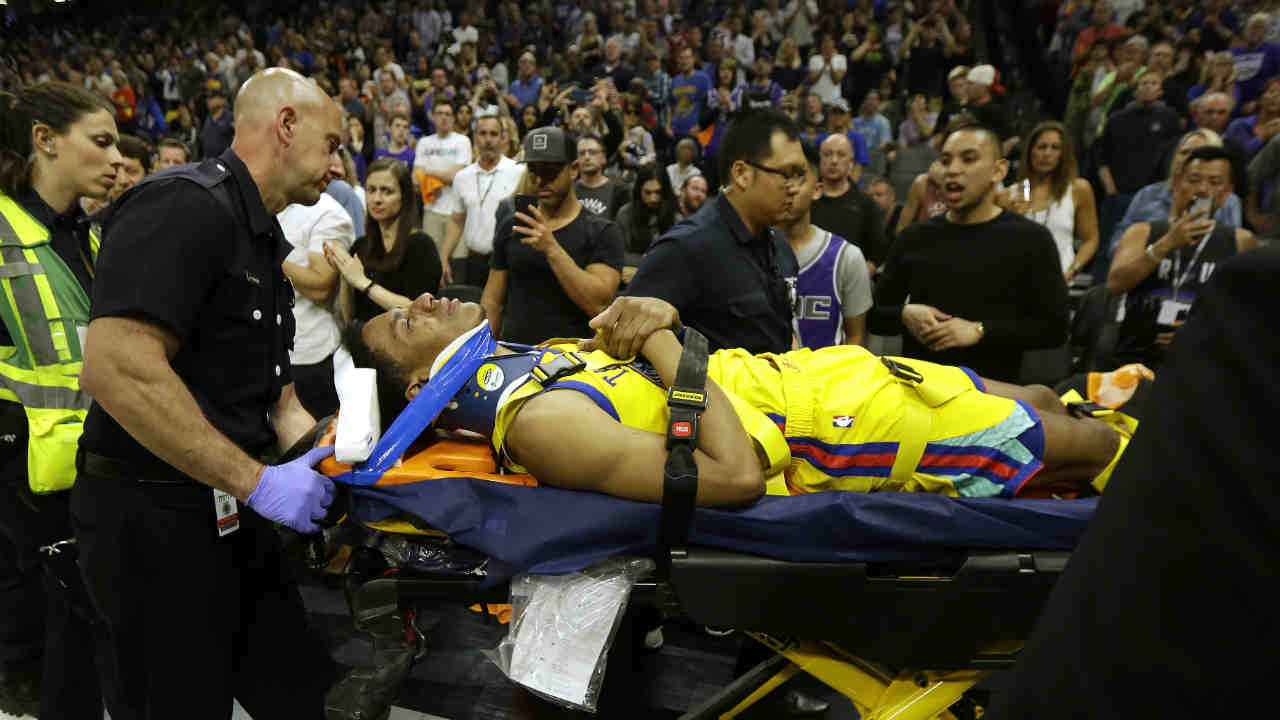 Golden State Warrior Patrick McCaw is taken off the court after falling following a foul by Sacramento Kings's Vince Carter Saturday, March 31, 2018, in Sacramento, Calif.