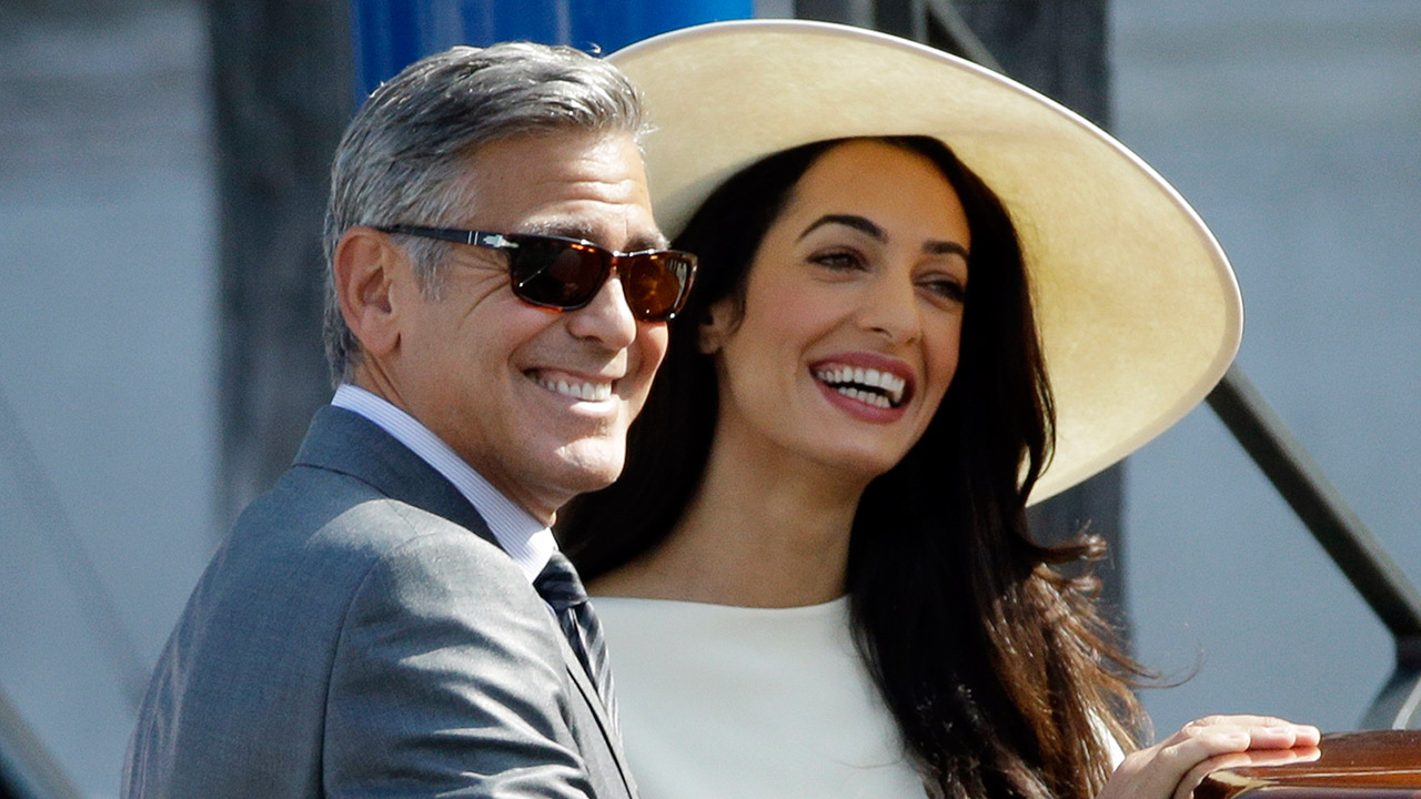 George Clooney and his wife Amal Alamuddin leave Venice's city hall after their civil marriage ceremony on Monday, Sept. 29, 2014.