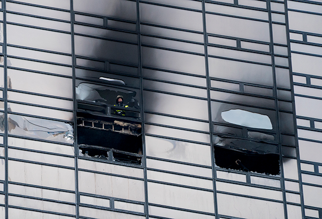 <div class='meta'><div class='origin-logo' data-origin='AP'></div><span class='caption-text' data-credit=''>A firefighter looks out from the window of a fire damaged apartment in Trump Tower in New York on Saturday, April 7, 2018. (AP Photo/Craig Ruttle)</span></div>