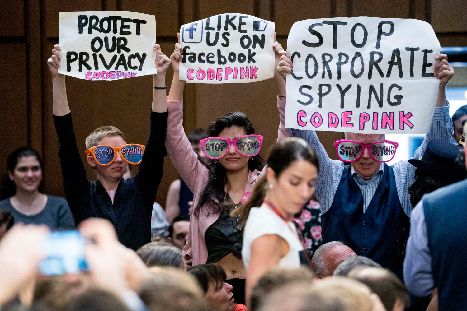 "<div class=""meta image-caption""><div class=""origin-logo origin-image none""><span>none</span></div><span class=""caption-text"">Members of the audience hold up signs and wear sunglasses that read ""Stop Spying"" before CEO Mark Zuckerberg arrives to testify. (Andrew Harnik/AP Photo)</span></div>"