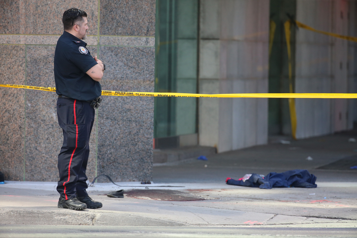 <div class='meta'><div class='origin-logo' data-origin='none'></div><span class='caption-text' data-credit='Steve Russell/Toronto Star via Getty Images'>Blood and clothing are on the Westside sidewalk at Park Home Avenue.</span></div>