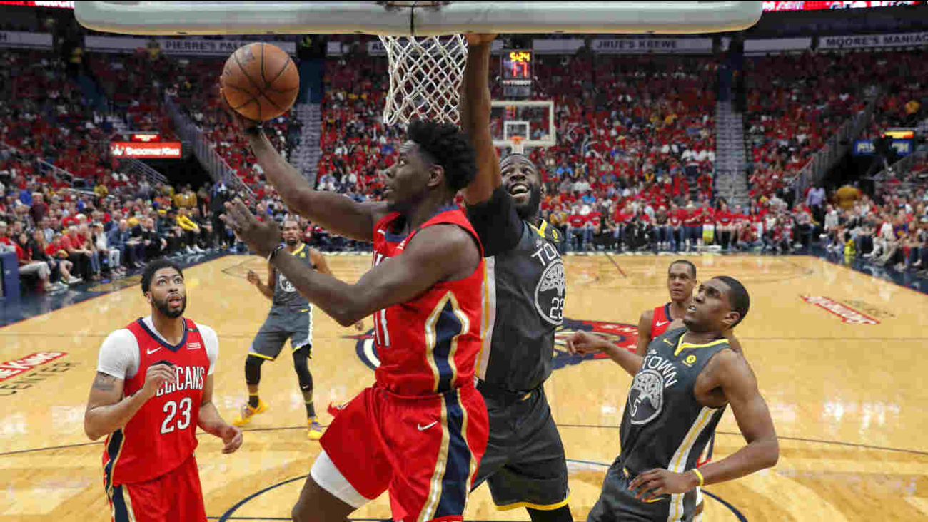 New Orleans Pelicans guard Jrue Holiday (11) goes to the basket against Golden State Warriors forward Draymond Green (23) in a NBA playoff game in New Orleans, Sunday, May 6, 2018.
