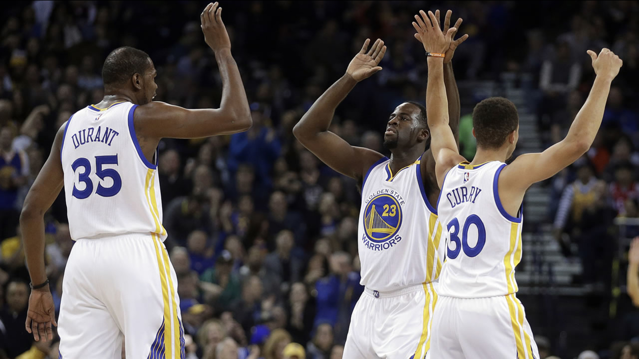 Golden State Warriors' Draymond Green celebrates a score against the Houston Rockets with Kevin Durant and Stephen Curry during a game on Dec. 1, 2016, in Oakland, Calif. (AP Photo/Ben Margot)