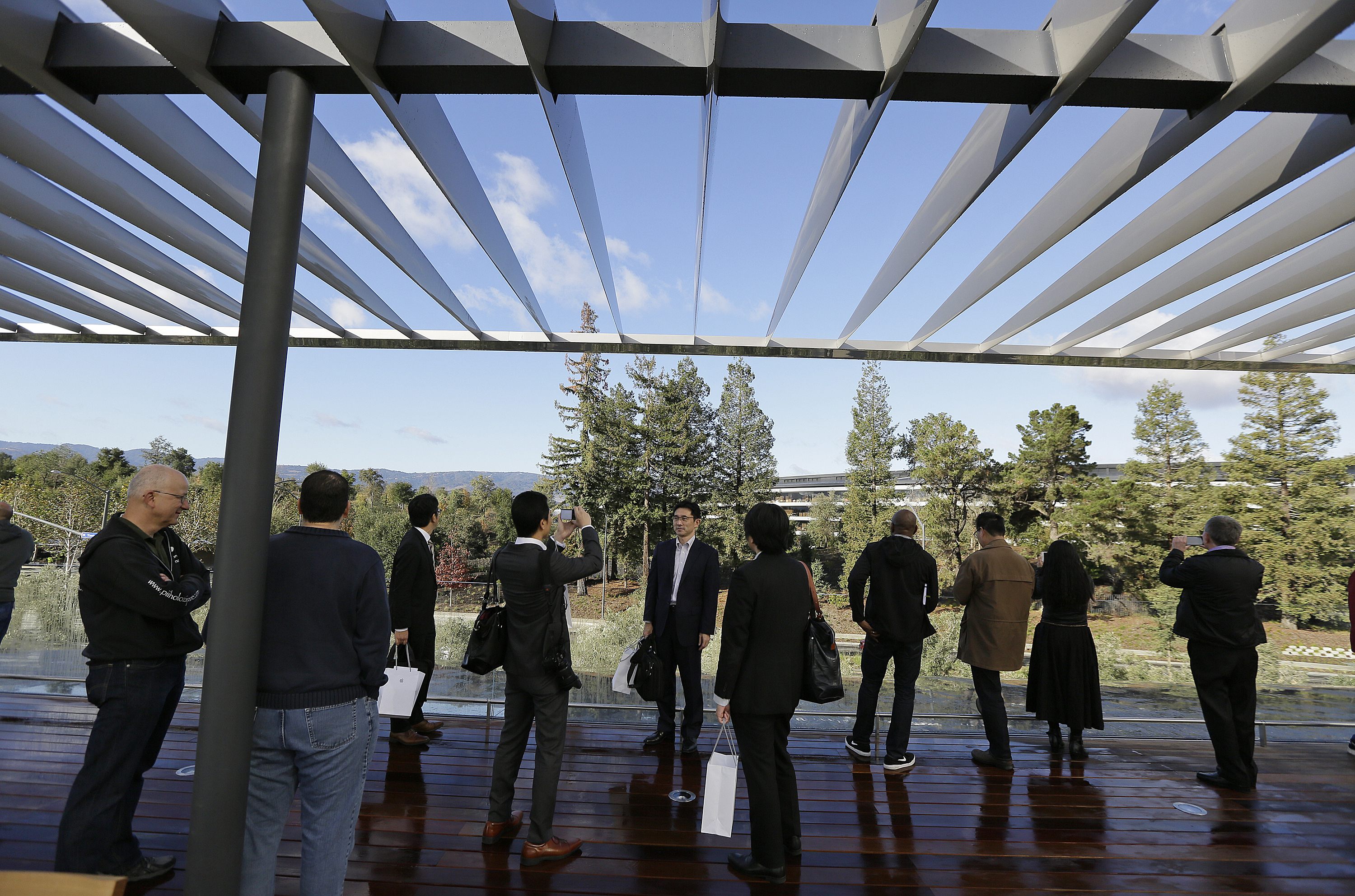 <div class='meta'><div class='origin-logo' data-origin='none'></div><span class='caption-text' data-credit='AP'>People stand on a rooftop terrace with the main building in the background during the grand opening of the Apple Park Visitor Center</span></div>