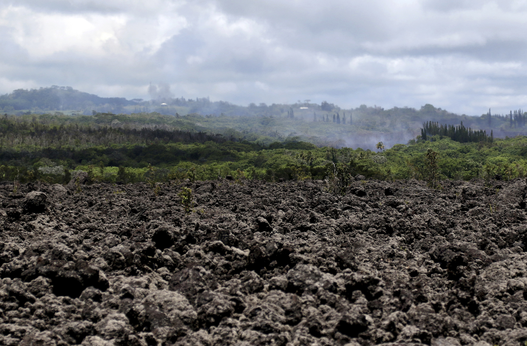 "<div class=""meta image-caption""><div class=""origin-logo origin-image ap""><span>AP</span></div><span class=""caption-text"">Volcanic gases and ash rise from recent lava fissures near Pahoa, Hawaii on Monday, May 14, 2018. The field of hardened lava rocks in the foreground is from previous eruptions. (AP Photo/Caleb Jones)</span></div>"