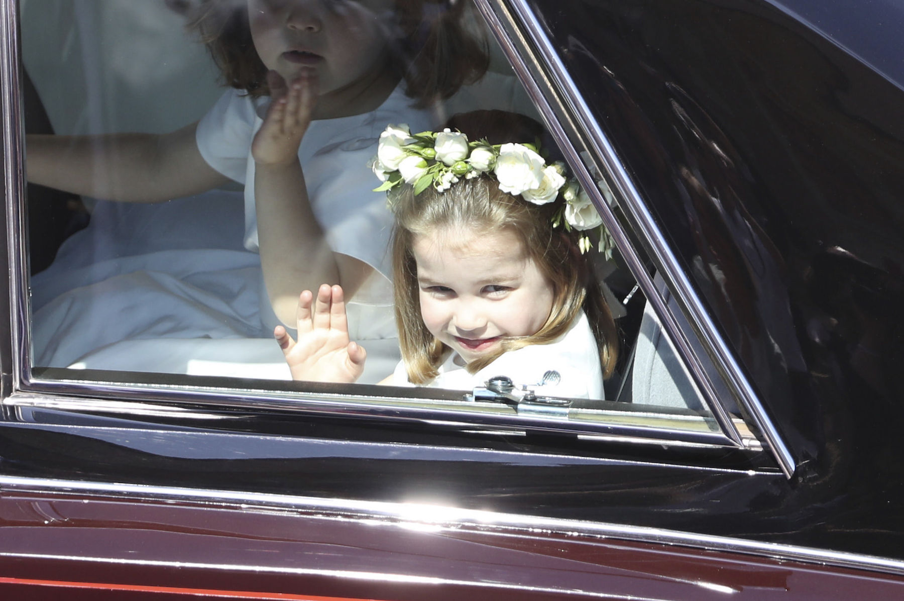 <div class='meta'><div class='origin-logo' data-origin='AP'></div><span class='caption-text' data-credit='Andrew Milligan/pool photo via AP'>Princess Charlotte waves as she rides in a car to the wedding ceremony of Prince Harry and Meghan Markle at St. George's Chapel in Windsor Castle in Windsor.</span></div>