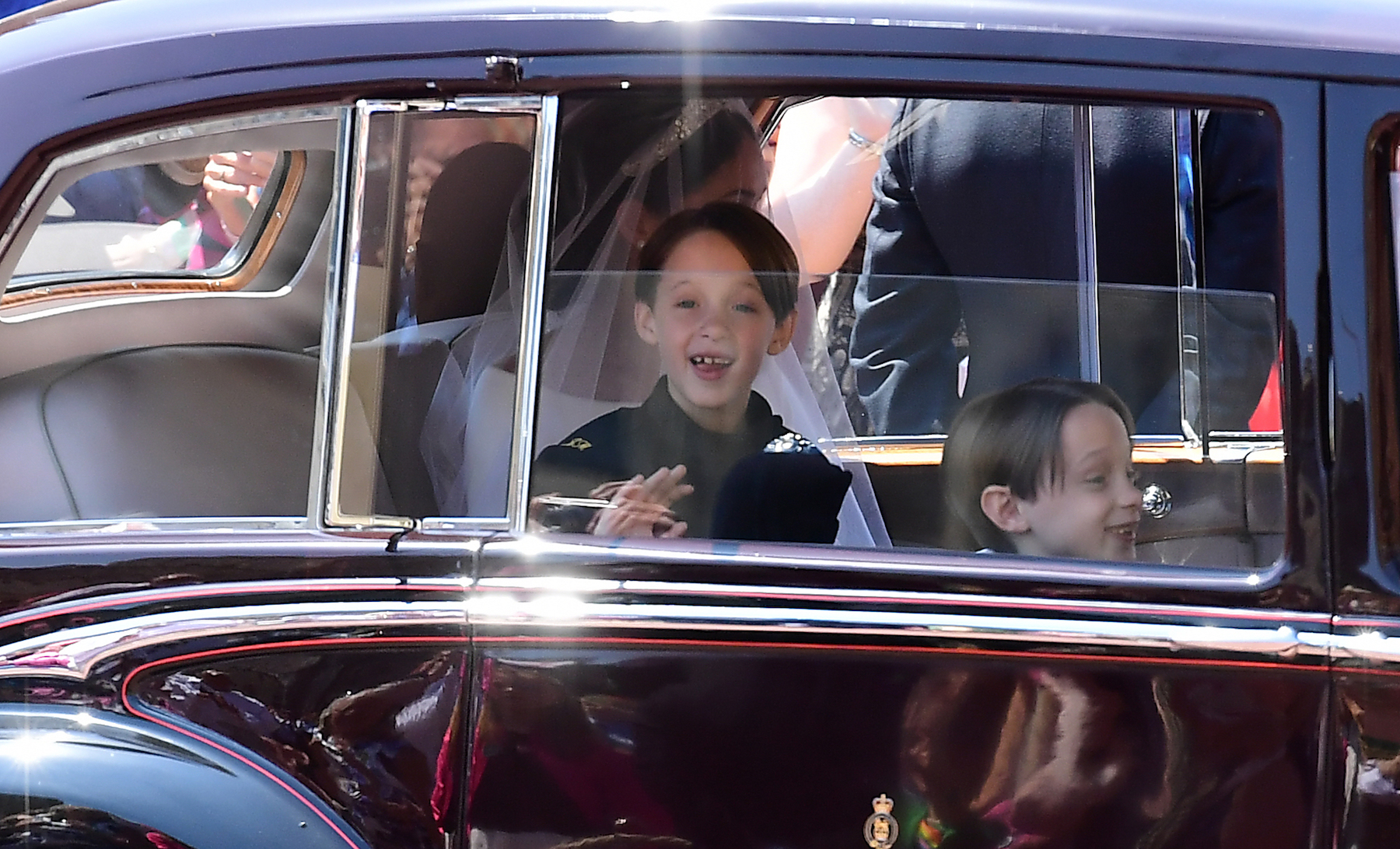 <div class='meta'><div class='origin-logo' data-origin='AP'></div><span class='caption-text' data-credit='Ian West/AFP/Getty Images'>Page boys John and Brian Mulroney accompany US actress Meghan Markle as she arrives in a car for the wedding ceremony to marry Britain's Prince Harry, Duke of Sussex.</span></div>