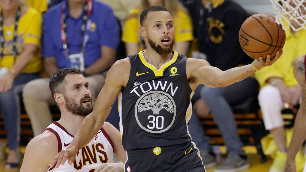 Warriors guard Steph Curry drives to the basket past Cavaliers forward Kevin Love in Game 2 of the NBA Finals in Oakland on Sunday, June 3, 2018.
