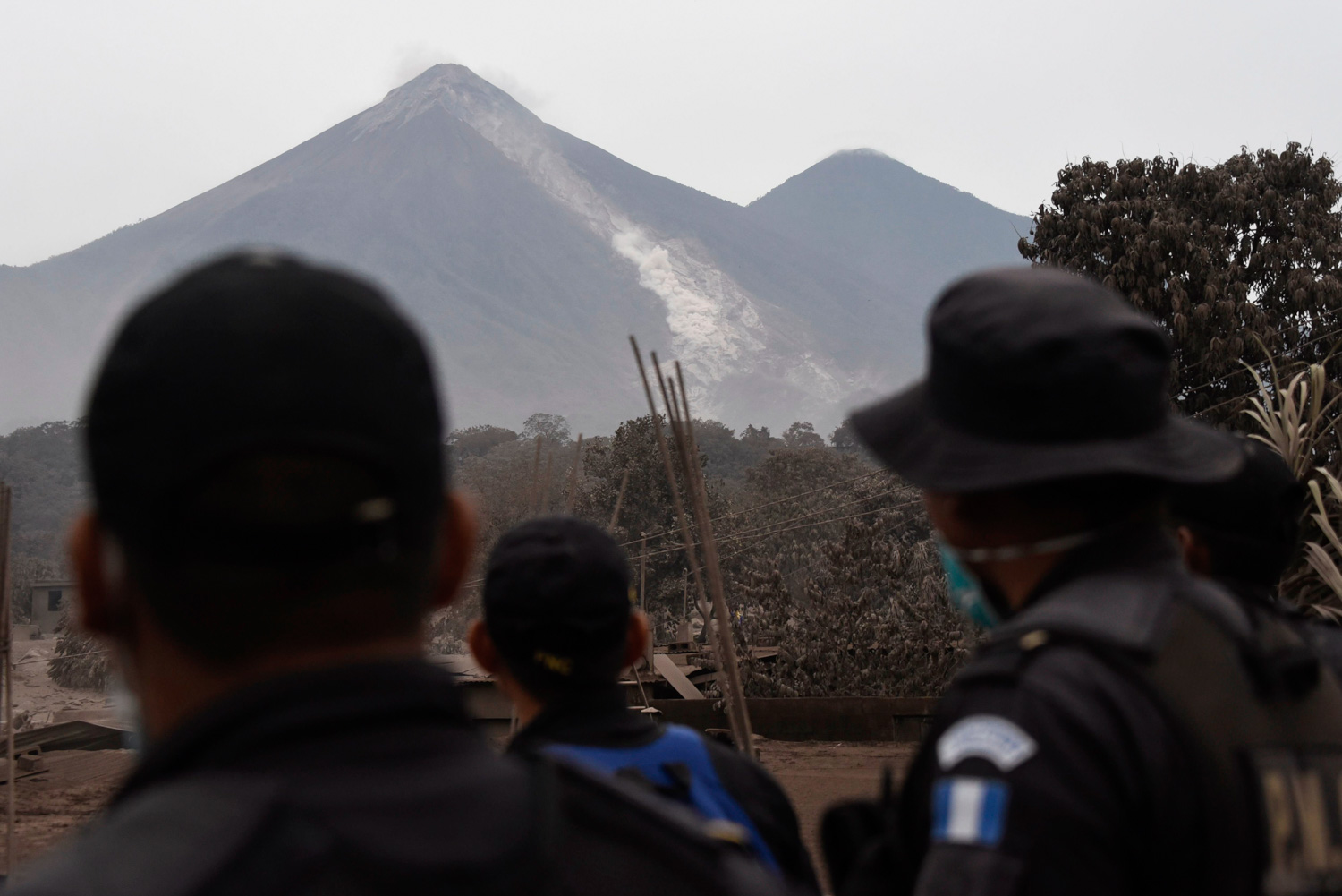 "<div class=""meta image-caption""><div class=""origin-logo origin-image none""><span>none</span></div><span class=""caption-text"">Police officers look at the Fuego Volcano from San Miguel Los Lotes, a village in Escuintla Department, about 35 km southwest of Guatemala City, on June 4, a day after an eruption. (JOHAN ORDONEZ/AFP/Getty Images)</span></div>"