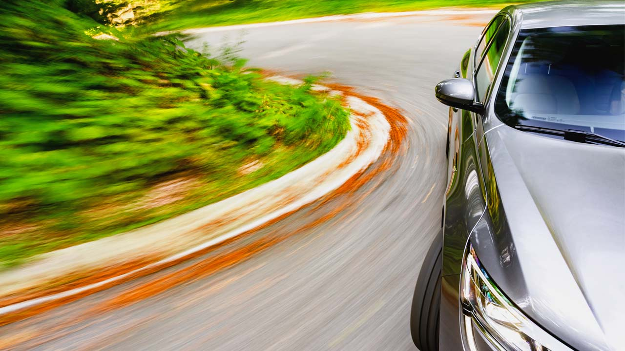 This generic image shows a car on a curvy road.