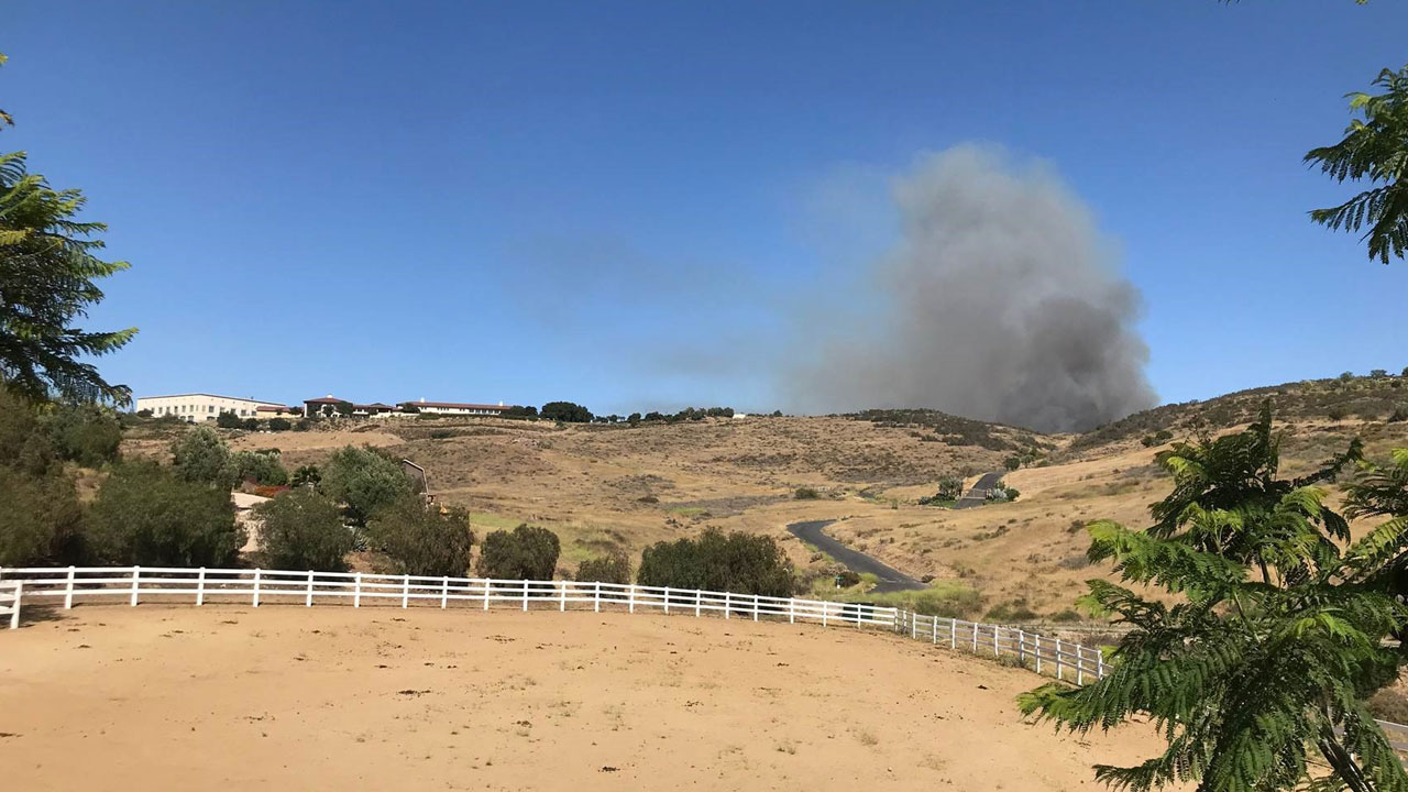Smoke billows from a small brush fire burning in a hillside in Simi Valley near the Wood Ranch neighborhood and Ronald Reagan Presidential Library.