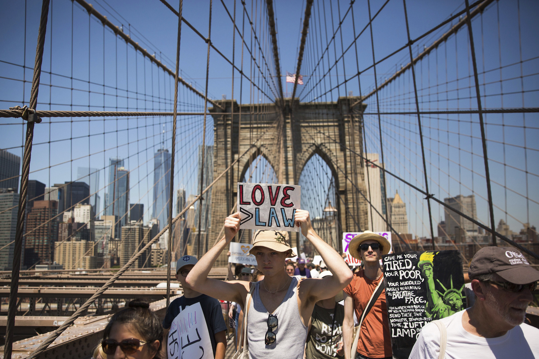 <div class='meta'><div class='origin-logo' data-origin='AP'></div><span class='caption-text' data-credit='AP Photo/Kevin Hagen'>Activists carry signs across the Brooklyn Bridge during a rally to protest the Trump administration's immigration policies Saturday, June 30, 2018, in New York, New York.</span></div>