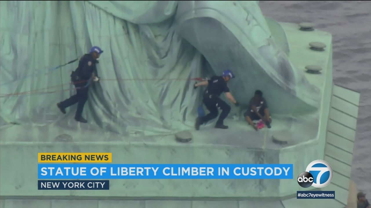 After more than two hours, police have apprehended a woman who climbed the base of the Statue of Liberty.