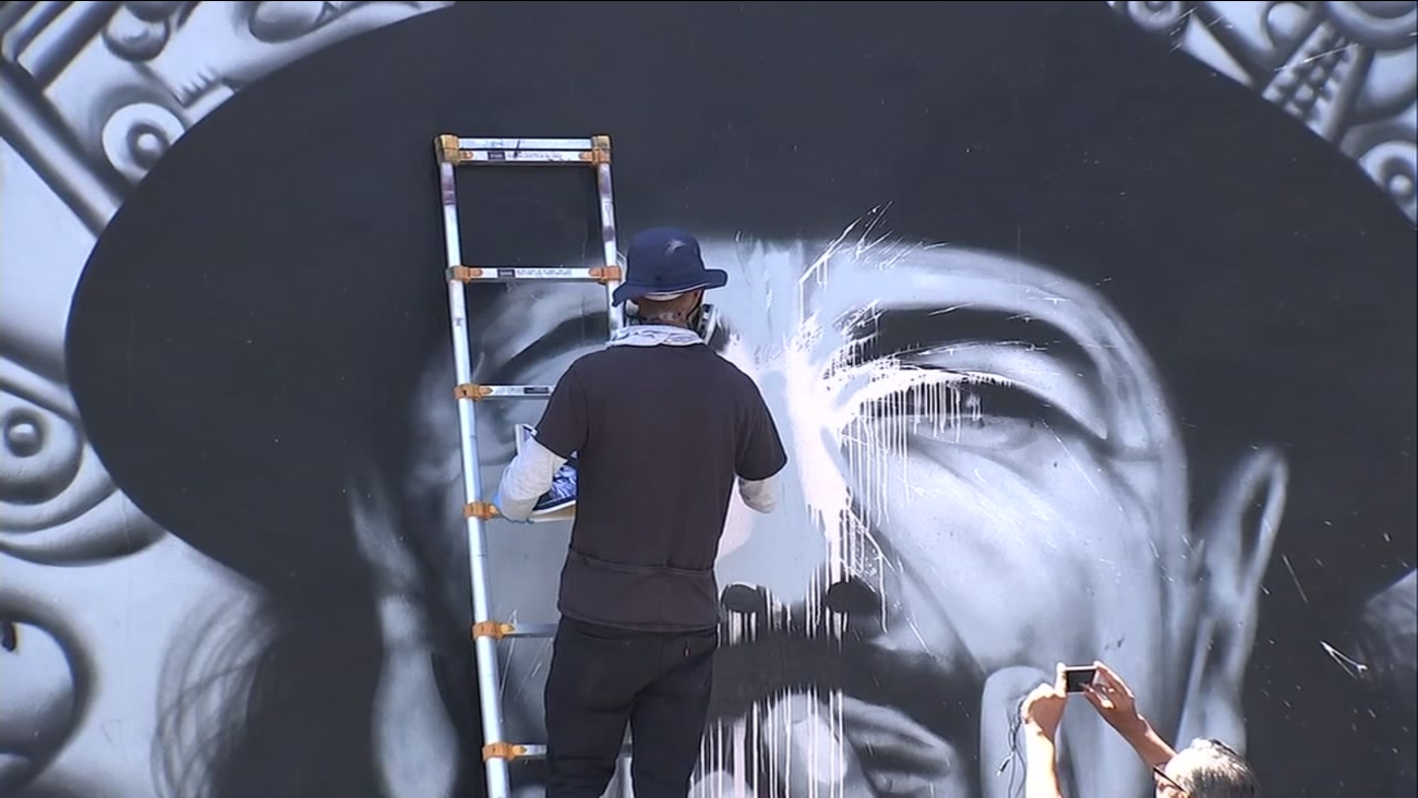 Mel Waters fixes damage to his Carlos Santana mural in San Francisco's Mission District on July 14, 2018.